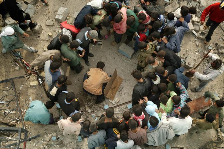 Iraker suchen kurz nach einem Bombenanschlag in Husseiniya den Anschlagsort nach Leichenteilen ab, wo sich ein Selbstmordattentäter in die Luft gesprengt hat; Foto: Michael Kamber