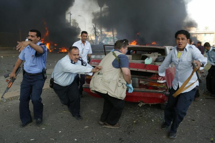 Männer bergen einen Wagen nach einem Sprengstoffanschlag eines Selbstmordattentäters vor dem Gebäude des Internationalen Roten Kreuzes in Bagdad im Oktober 2003; Foto: Michael Kamber