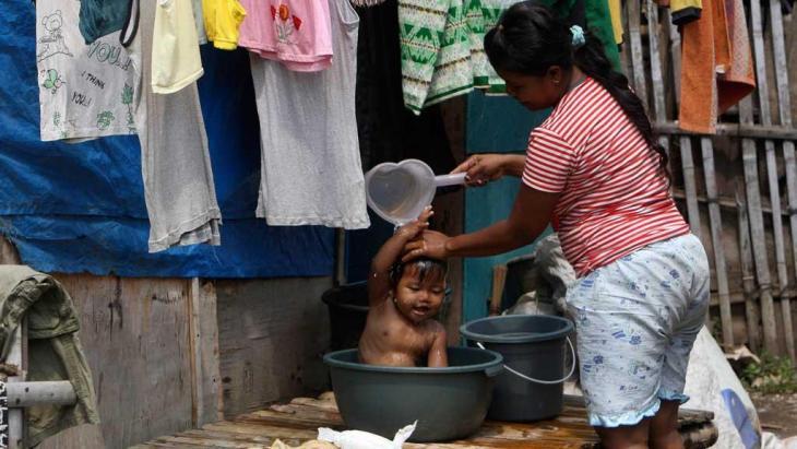 Eine Frau wäscht ihr Kind vor ihrer Hütte in einem Slum in der indonesischen Hauptstadt Jakarta; Foto: AP