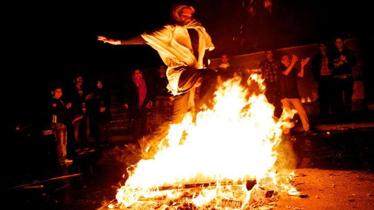 Eine Frau springt im Rahmen der Chaharshanbeh-Soori-Festlichkeit über eine Flamme; Foto: Behrouz Mehri/AFP/Getty Images