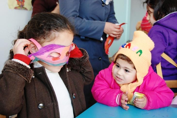Children making paper masks in a kindergarten for traumatised children  in Manshia, Jordan (photo: Laura Overmeyer)