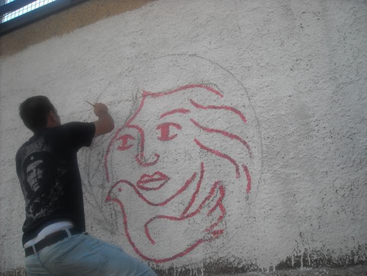Mann zeichnet Logo der Palestinian Working Women's Society for Development (PWWSD) auf eine Wand; Foto: Palestinian Working Women's Society for Development (PWWSD)