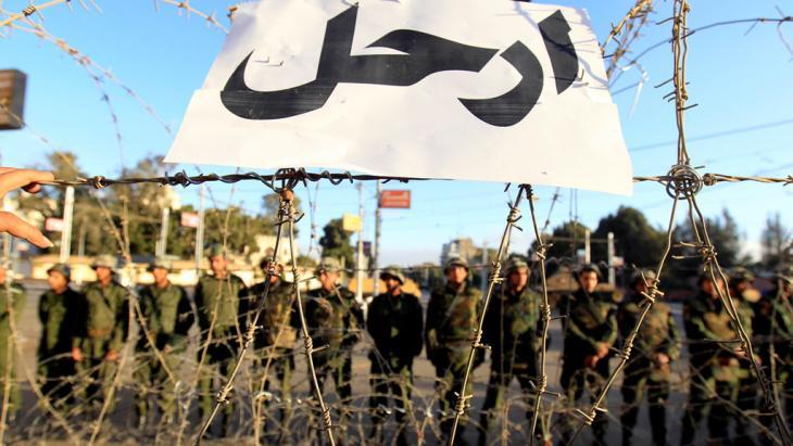 """Armeeeinheiten vor Stacheldraht und einem Plakat mit der Aufschrift """"Hau ab!"""" vor dem Präsidentenpalast in Kairo im Dezember 2012; Foto: Reuters"""