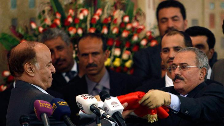 Jemens Präsident Abd-Rabbu Mansour Hadi bekommt am 27.2.2012 die jemenitische Fahne von Ali Abdullah Salih in Sanaa überreicht; Foto. Reuters