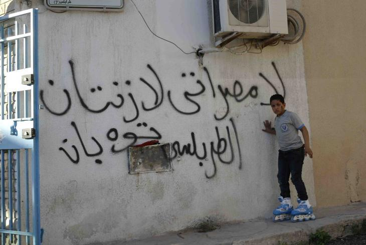 """A boy on roller skates in front of graffiti that reads """"No Misrata, no Zintan"""" (photo: Valerie Stocker)"""