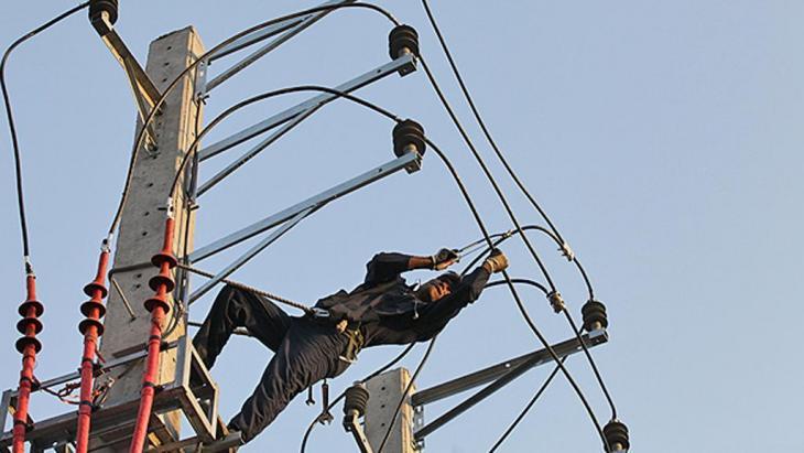 Afghanischer Arbeiter repariert einen Strommast in Teheran; Foto: ILNA