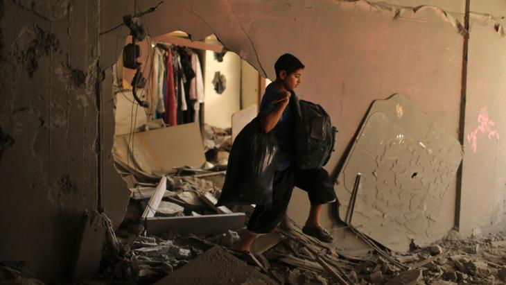 Ein palästinensischer Junge trägt seine Habseligkeiten im zerstörten Haus seiner Familie in Gaza Stadt, 16. Juli 2014; Foto: REUTERS/Mohammed Salem