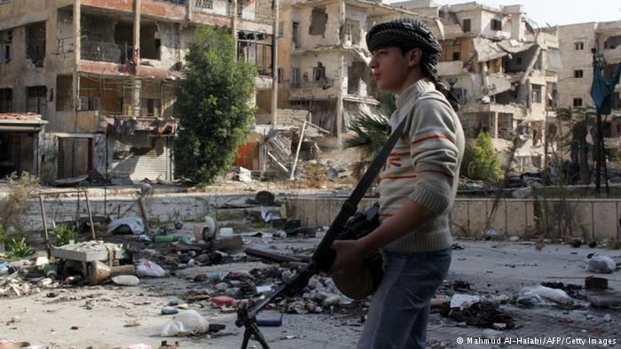 A young combatant stands in front of a row of bombed-out buildings in Syria (photo: AFP/Getty Images)
