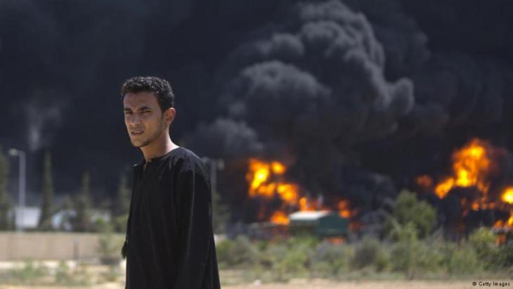 Ein junger Araber vor dem brennenden Kraftwerk. Bei Bombenangriffen auf das einzige Kraftwerk in Gaza durch die israelische Armee wurde ein Generator beschädigt und Treibstofftanks entzündet. Ein Drittel der Haushalte sind derzeit ohne Strom; Foto: Getty Images