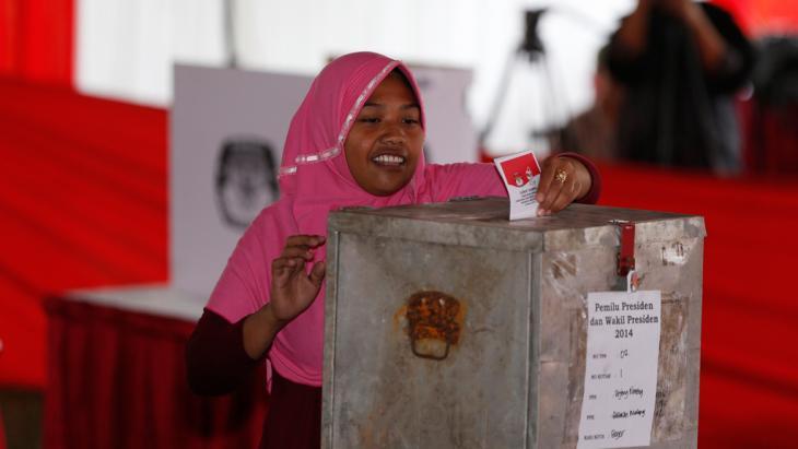 Eine Frau wirft ihren Wahlzettel in die Urne; Foto: Reuters
