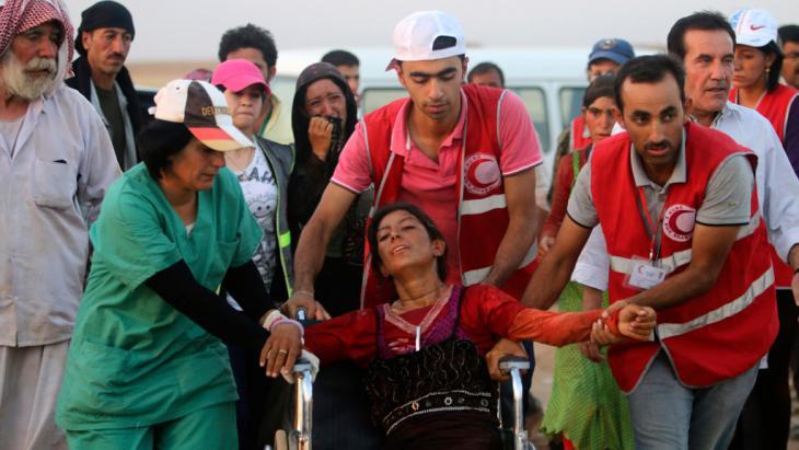 Mitglieder des Kurdischen Roten Halbmondes helfen einer jesidischen Frau; Foto: Reuters