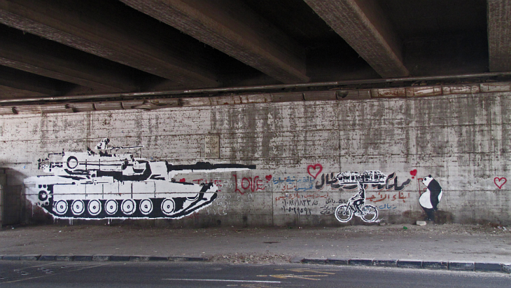 "Graffiti ""Tanks-vs-Bike"" von Ganzeer & Sad Panda"