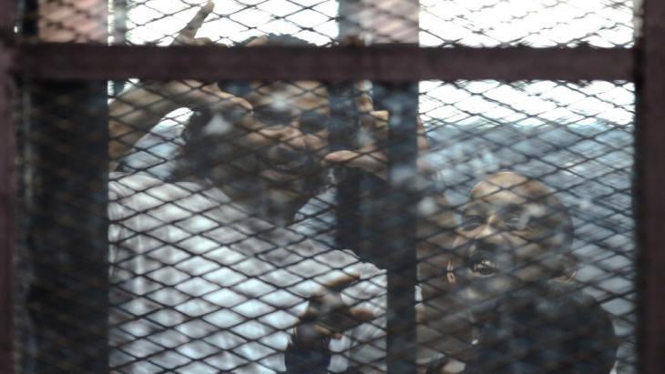 Alaa Abdel-Fattah (l.) und Mohamed el-Shahed in einem Gefängniskäfig in einem Gerichtssaal in Kairo; Foto: Getty Images/AFP