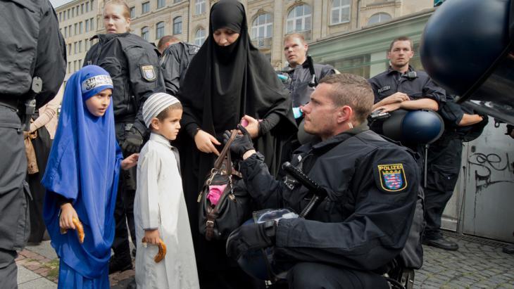 Anhängerin von Pierre Vogel bei Taschenkontrolle durch Polizisten vor der Kundgebung am 07.09.2014; Foto: picture-alliance/dpa/B. Roessler