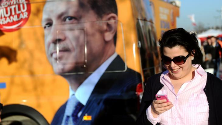 Eine Türkin vor einem Plakat, das das Gesicht Erdogans zeigt; Foto: OZAN KOSE/AFP/Getty Images