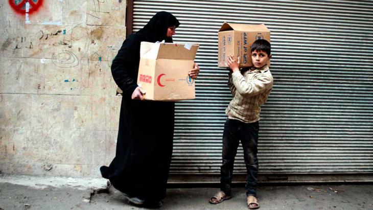 eine syrische Frau und ihr Sohn transportieren Kartons mit Lebensmitteln in der nordsyrischen Stadt Aleppo.