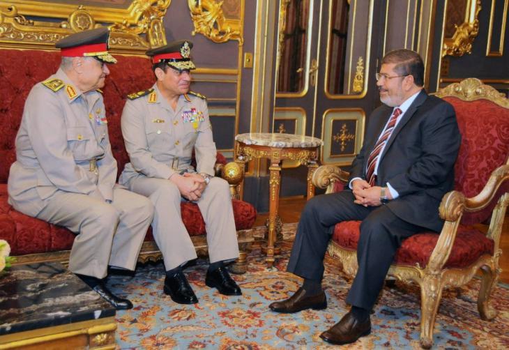 Der ehemalige ägyptische Präsident Mursi (r.)  im Gespräch mit damaligen Verteidigungsminister Al-Sisi (m.) im Dezember 2012; Foto: dpa