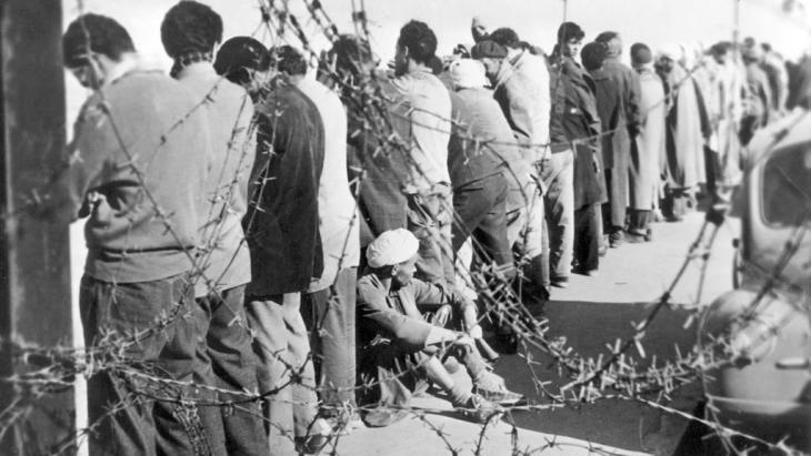 Festgenomme Algerier stehen im Dezember 1956 in Oran mit den Gesichtern zur Wand an der Stadtmauer und warten darauf, verhört zu werden; Foto: dpa/picture-alliance
