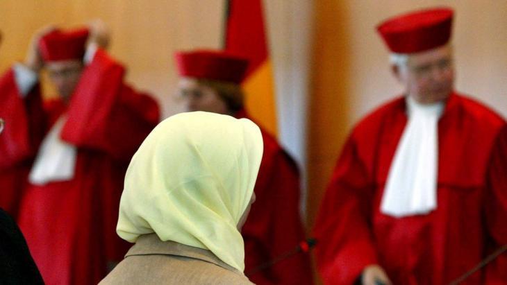 Fereshta Ludin, muslimische Lehrerin und Beschwerdeführerin im Kopftuch-Streit, sitzt am 24.09.2003 nach der Urteilsverkündung im Bundesverfassungsgericht in Karlsruhe vor den Richtern; Foto: picture-alliance/dpa/U. Deck