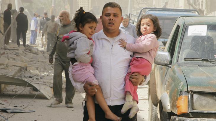 Nach einem Fassbombenabwurf von Kampfjets des Regimes auf ein Wohnviertel in Idlib rettet ein Mann zwei traumatisierte Kinder aus den Trümmern der Häuser; Foto: Reuters/Ammar Abdullah
