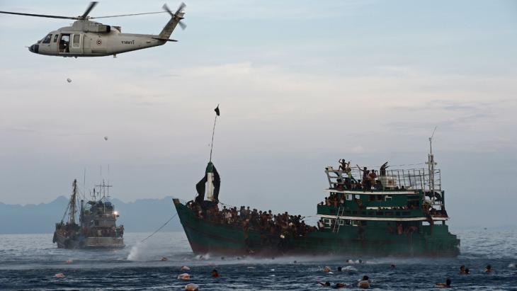 Ein thailändischer Armeehelikopter wirft Nahrungsmittel für die im Meer festsitzenden Flüchtlinge, die muslimische Minderheit der Rohingya, ab. Foto: Getty Images/ AFP/ C. Archambault