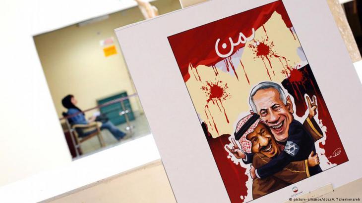Karikaturmotiv: Israels Ministerpräsident Benjamin Netanjahu wird vom saudischen König umarmt. Im Hintergrund eine Landeskarte des Jemen mit blutigen Einschusslöchern; Foto: picture-alliance/ dpa/ A. Taherkenareh