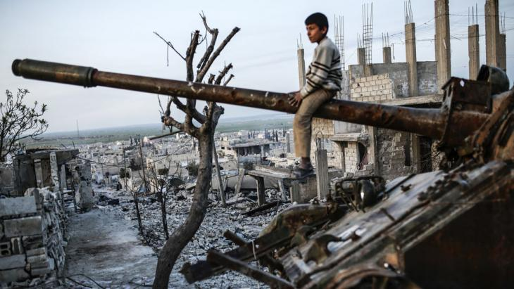 Junge auf Panzer im zerstörten syrischen  Ain al-Arab; Foto: Getty Images/AFP/Y. Akgul