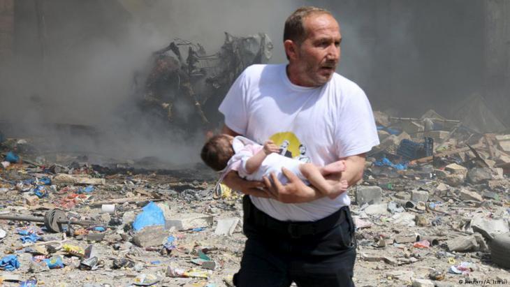 Syrischer Zivilist rettet ein Baby nach einem Fassbombenabwurf in Aleppo; Foto: Reuters/A. Ismail