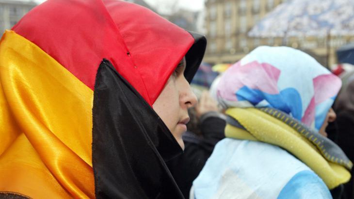 """Frau mit Deutschland-Flagge auf einer Demonstration gegen das Kopftuchverbot und """"Pseudo-Pressefreiheit"""" in Deutschland. Foto: picture-alliance/dpa"""