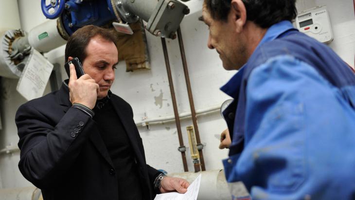 Der türkische Unternehmer Taskin Akkay  telefoniert in München, während er einem Mitarbeiter den Einbau einer Heizung erklärt; Foto: Marc Müller/dpa