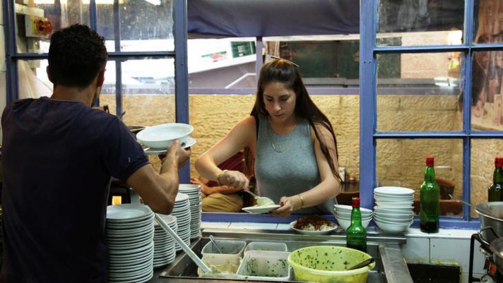 """Die Kellnerin Natalie Geva beim Servieren von Hummus im Restaurant """"Azura""""; Foto: DW/S. Sinico"""