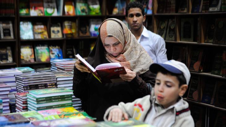 Ägypterin liest an einem Buchstand in Kairo; Foto: imago/Xinhua