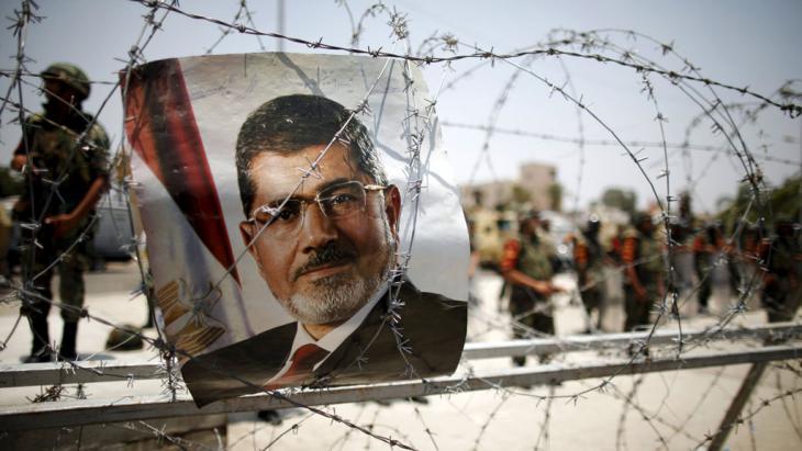 Plakat Mursis vor einer Absperrung des ägyptischen militärs in Kairo; Foto: picture-alliance/dpa/K. Elfiq