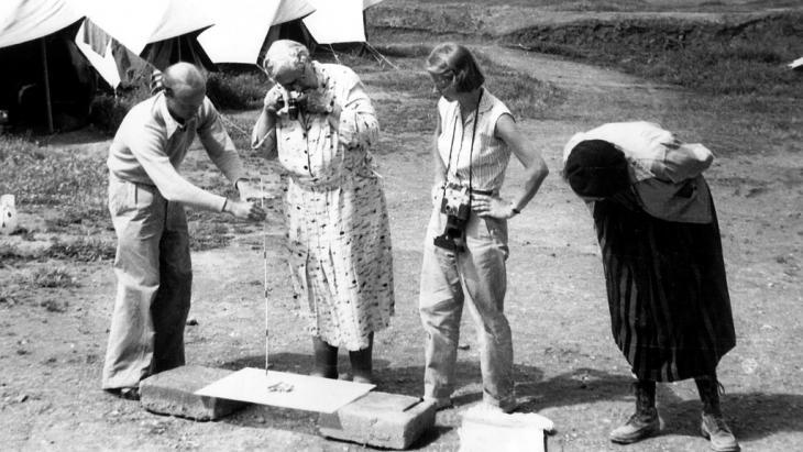 Die britische Krimi-Autorin Agatha Christie (m.) fotografiert auf dem Gelände in der alten Assyrer-Stadt Nimrud im Irak eine kleine ausgegrabene Elfenbeinfigur; Foto: picture-alliance/dpa