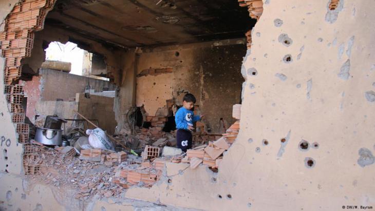 Ein kurdisches Kind in einem zerstörten Wohnhaus; Foto: DW