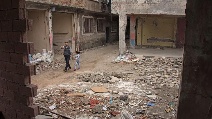 Mann mit Kind geht zwischen Trümmern im Bezirk Sur in Diyarbakir; Foto: DW