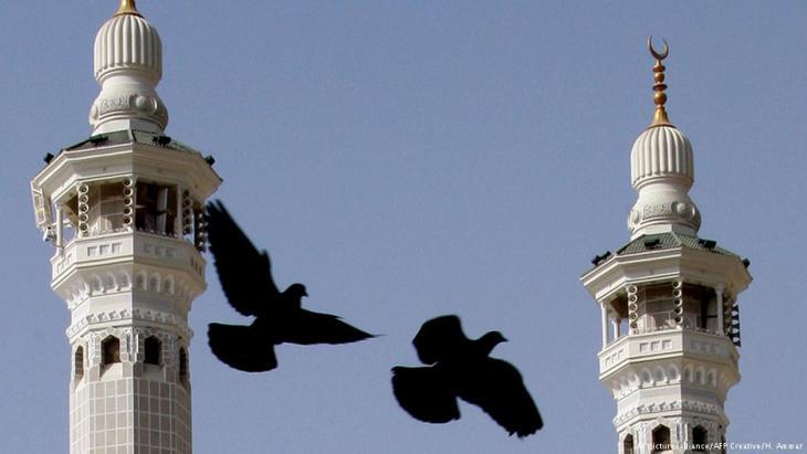 Tauben fliegen von einer Moschee in Saudi-Arabien (Foto: picture-alliance/AFP Creative/H. Ammar)