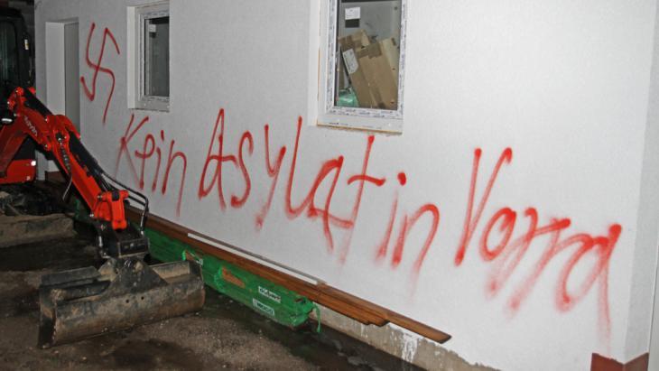 """Der Schriftzug """"Kein Asylant in Vorra"""" steht am 12.12.2014 in Vorra (Landkreis Nürnberger Land) an einer Hauswand. In drei als Flüchtlingsunterkunft vorgesehenen Gebäuden hatte es in der Nacht zu Freitag gebrannt; Foto: picture-alliance/dpa/ToMa"""
