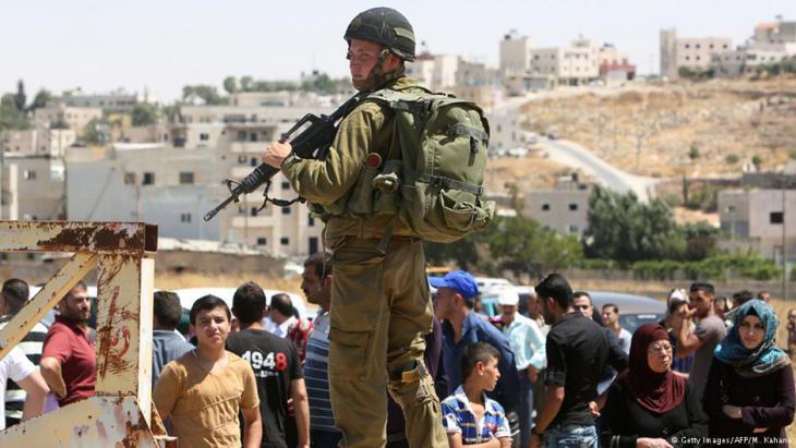 Israelischer Soldat bewacht einen Checkpoint vor wartenden Palästinensern im Süden Hebronsr guarding a checkpoint south of Hebron
