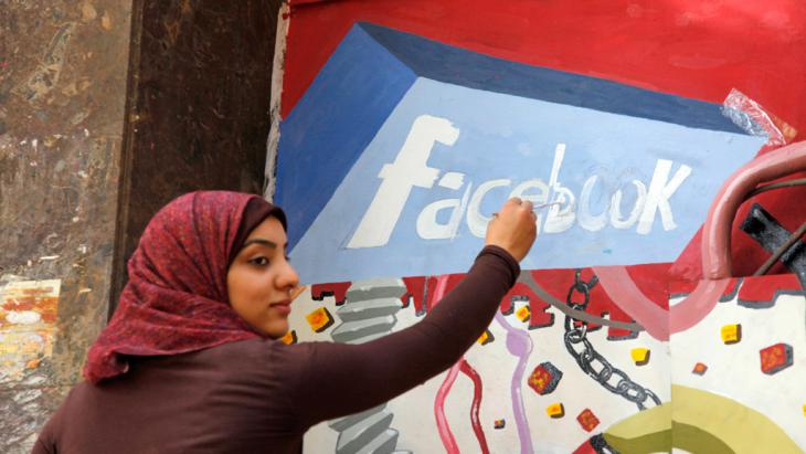 Kunststudentin der Universität Helwan zeichnet ein Facebook-Logo an einer Gedanktafel anlässlich des Sturzes von Hosni Mubarak in Ägypten; Foto: picture alliance/AP/M. Deghati