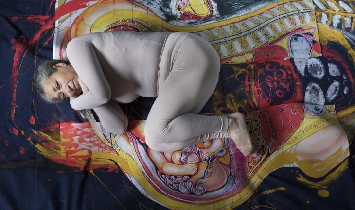 Eine ältere Teilnehmerin des Fotoprojekts liegt in Embryonalstellung auf einem bemalten Untergrund; Foto: Khalifi