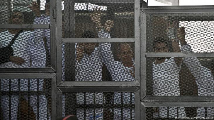 Inhaftierte Al-Jazeera-Journalisten während ihres Verfahrens im März 2014 in einem Käfig in Kairo; Foto: AFP/Getty Images