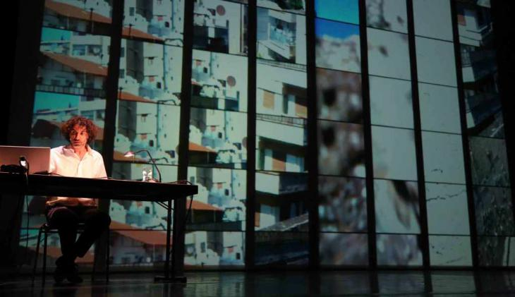 Mroué sitzt vor einer Projektionswand während The Pixelated Revolution;source:kampnagel.de