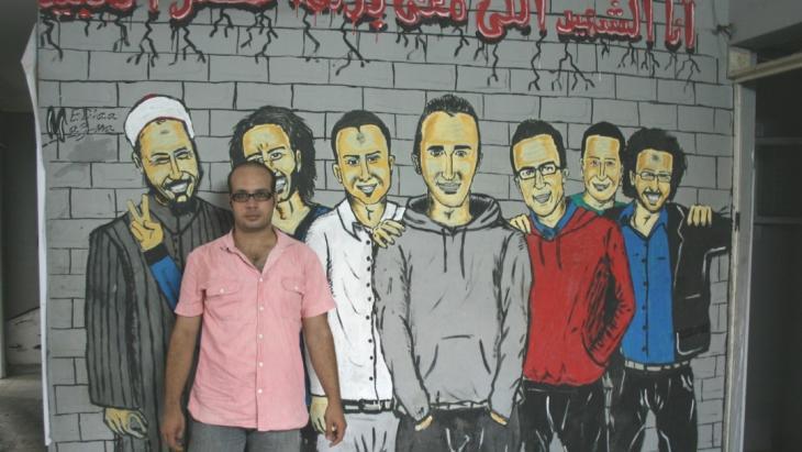 Ahmed Maher vor einem Revolutionsgrafitti in Kairo; Foto: Markus Symank