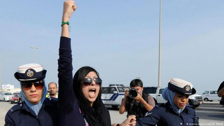 Bahraini rights activist Zainab Al-Khawaja being arrested by two police women while on a march