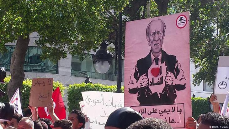 """Plakat mit dem Bild Beji Said Essebsis und dem Schriftzug """"Ich liebe Korruption"""" während der Manich Msameh Demonstration im Zentrum von Tunis am 13.5.2017; Foto: DW/Sarah Mersch"""