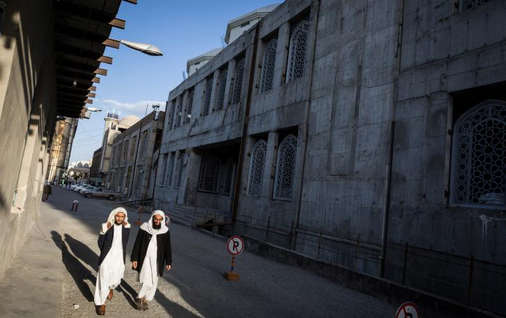 Zwei Schüler der Jamiah Darul Uloom spazieren neben dem Rohbau der Makki-Moschee in Zahedan; Foto: Philipp Breu