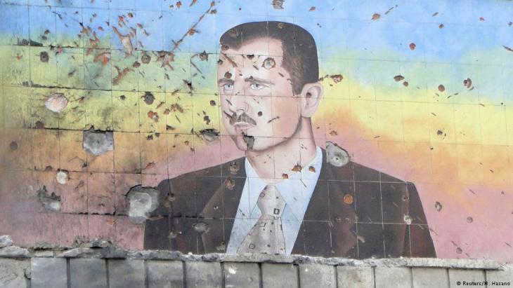 Zerschossene Fassade einer Polizeiakademie in Aleppo mit dem Bild Assads; Foto: Reuters