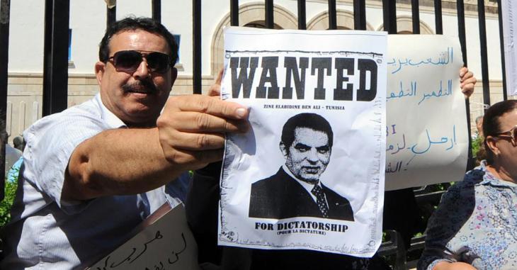 """Tunesier hält Plakat mit der Aufschrift """"Wanted: Ben Ali - Tunesien""""; Foto: AFP"""