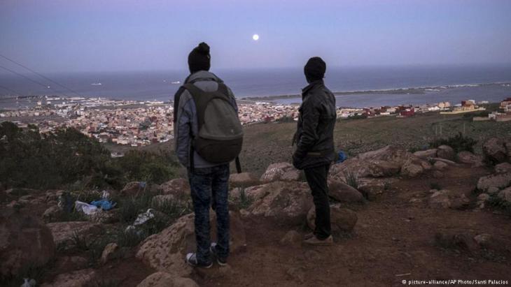 Flüchtlinge in der marokkanischen Provinz Nador blicken auf die spanische Exklave Melilla, Foto: picture-alliance/AP